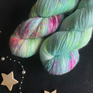 soft blue single spun lace yarn with white flashes and speckles of neon pink, neon yellow and neon orange on a black background