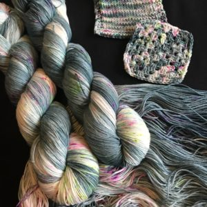 deep teal green base yarn with white flashes, speckled with pink , aqua and neon green