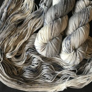 silver grey yarn with blue and brown speckles, two twisted skeins are on top of an untwisted one