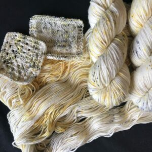 natural yarn speckled with grey and yellow. twisted skeins lay on an untwisted skien, with swatches also shown
