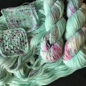 minty yarn with black and pink speckles laid out with twisted skeins and swatches on top