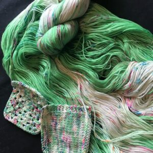 bright green yarn with white flashes and speckles of pink, orange and blue. one skein is laid flat, one is twisted and swatches are shown