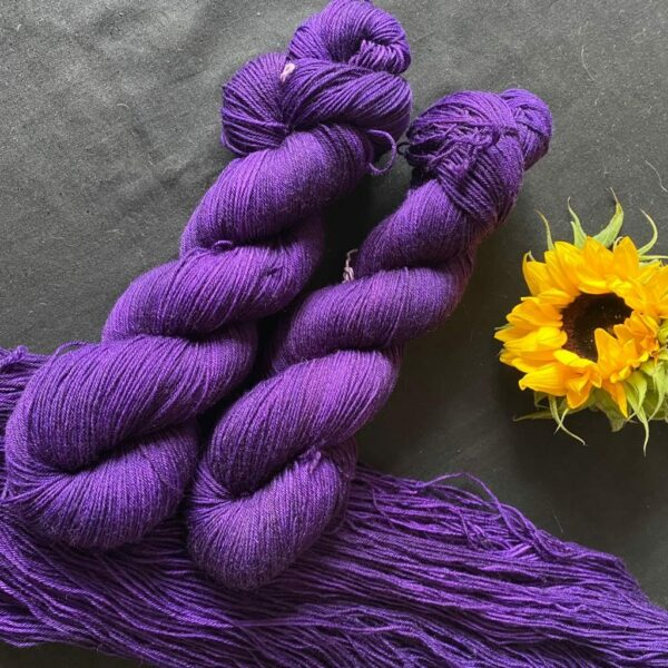 deep cadbury purple semi solid yarn, shown twisted and untwisted on a black background. A sunflower is also in the shot.