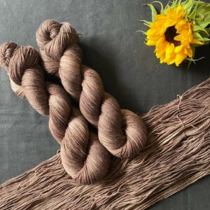 dark chocolate brown semi solid yarn, shown twisted and untwisted on a black background. A sunflower is also in the shot.