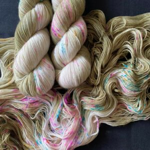 delicate lichen/mossy coloured yarn, with golden undertone. the yarn has white sections and speckles of neon pink and blue