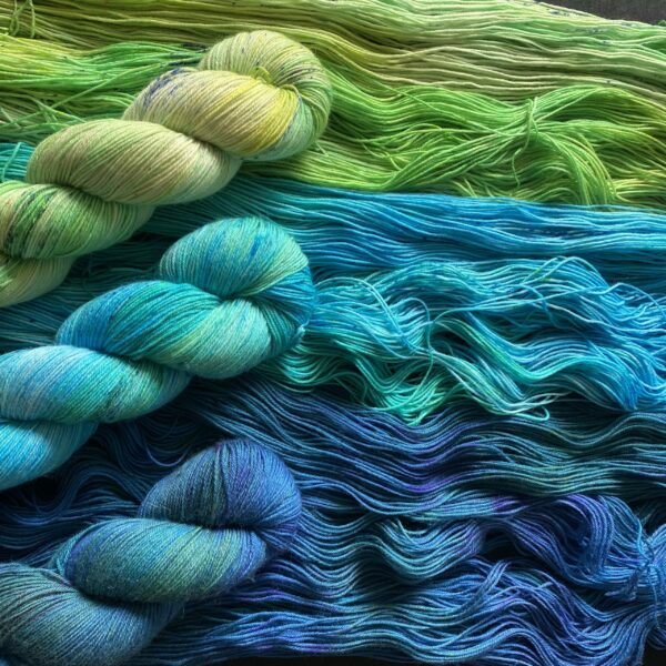 three different twisted skeins on top of untwisted skeins. On is a tonal bright green, one is a mid blue/jade and the bottom one is a dark blue/green.