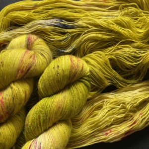 yellowy olive yarn with black and red speckles. two twisted skeins on an opened skein.
