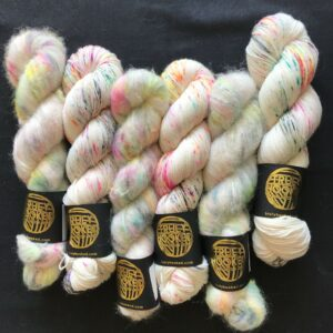 twisted skeins of white yarn speckled with neon pinks, yellows, greens, oranges and black , on a black background.