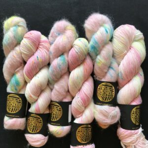 soft pale pink yarn speckled with carribean blue, neon orange and neon yellow. twisted skeins are side by side on a black background.