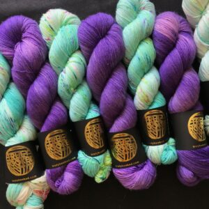 alternating skeins of deep cadbury purple, and aqua green with speckles of dark blue, pink and yellow. skeins are shown on a black background