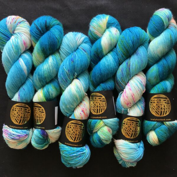 vibrant carribean blue skeins with flashes of white and speckles of neon purple, neon orange and neon green are arranged side by side on a black background.