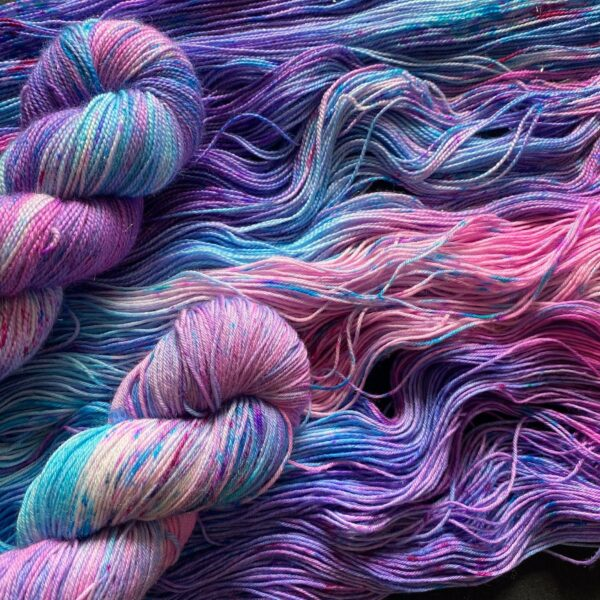 pink, purple and blue marbled yarn, twisted skeins laid over untwisted ones to show the colours