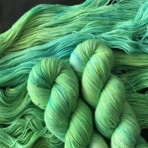 sparkle yarn in shades of darker and yellowy green. two twisted skeins are on an opened skein