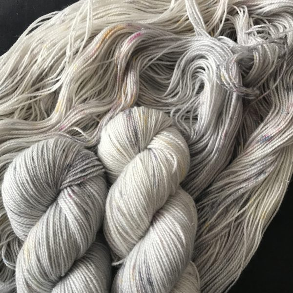 very pale silvery yarn with speckles of grey, yellow and blue.