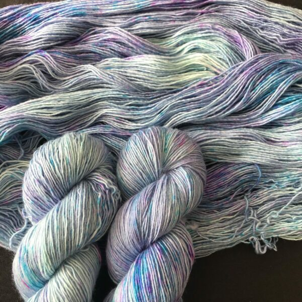 twisted and untwisted skeins in a very soft aqua speckled with aquas, pinks and lilacs. the colours are pastel, whimsical.