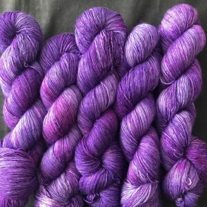 5 skeins of dark, cadbury purple yarn, with tonal variations of lighter and darker shades, with some pinker areas.