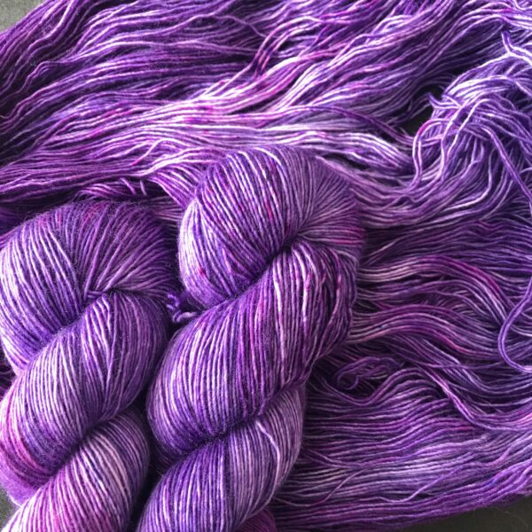 twisted, and untwisted skeins of dark, cadbury purple yarn, with tonal variations of lighter and darker shades, with some pinker areas.