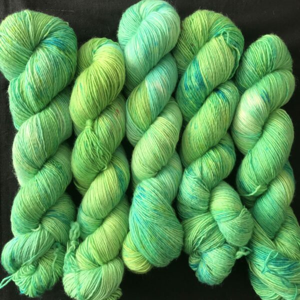 a tonal blend of yellow/green and aqua/green shades, with darker and lighter areas. 5 twisted skeins on a back background. the skeins fill the screen.