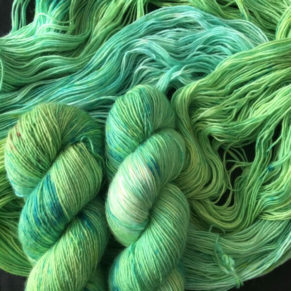 a tonal blend of yellow/green and aqua/green shades, with darker and lighter areas. two twisted skeins are laid on an open skein.