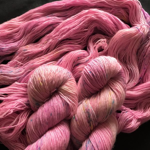 twisted and untwisted skeins of pinky yarn with speckles of pink and blue