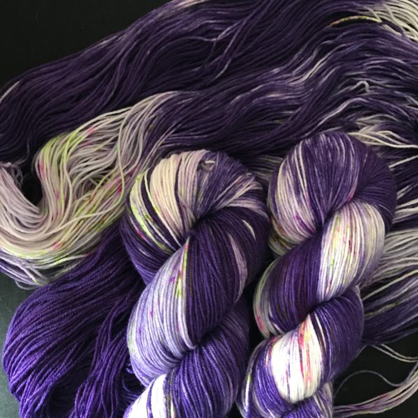 deep cadbury purple yarn with white sections, speckled with neon purple and neon green
