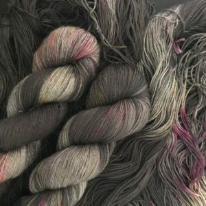 silvery grey yarn with areas dyed black and speckled with neon pink, neon orange, neon yellow.