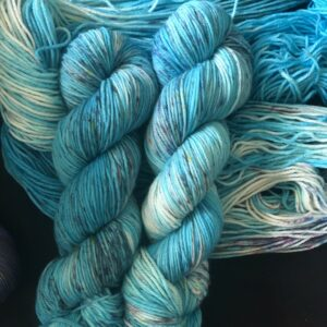 carribean blue base yarn with white flashes, darker and lighter areas. speckled with greys, yellows and pinky reds.