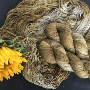 golden yellowish brown yarn with flashes of silvery undyed yak, speckled with brown and orange is shown twisted and untwisted. a partially opened sunflower is itowards the bottom left of the image