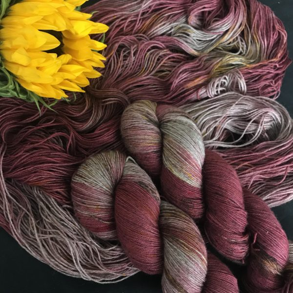 sliver grey yak yarn is dyed a deep red, with undyed flashes showing through.. The yarn is speckled with browns and yellows. Two twisted skeins are on top of an untwisted skein. A large partially opened sunflower is in the top left.
