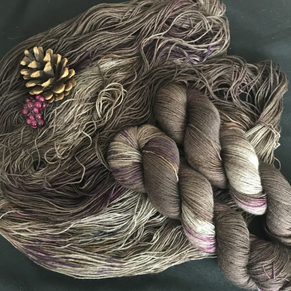 dark chocolatey borne yarn with flashes ion slivery yak is shown twisted and untwisted on a black background. the yarn is speckled with pinks and oranges. There are pine cones and fake pine berries at the top left corner.