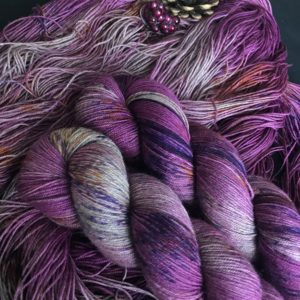 rich, pinky purple yarn with flashes of silvery yak, speckled with purples and oranges is shown twisted and untwisted. a pine cone is just peaking into the top of the shot.