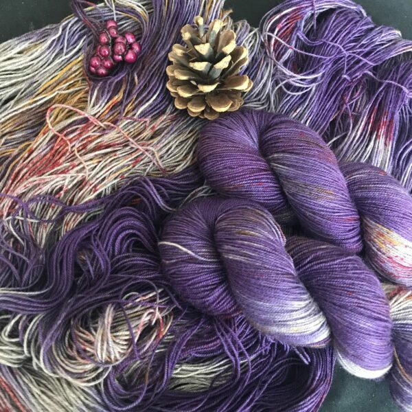 rich, cadbury purple yarn with flashes of silvery yak, and speckled with red s and golds. Skeins are shown twisted and untwisted with pine cones and fake pink berries at the top of the image.