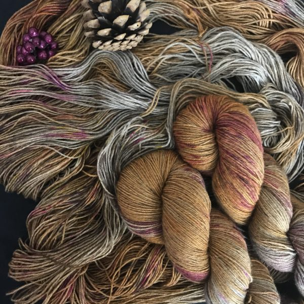 a soft orangey, yellow yarn with flashes of undyed silver yak, speckled with pinks and reds. Two twisted skeins are placed on an untwisted skien. A pine cone and fake pink berries are at the top left of the image.