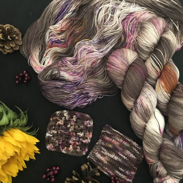 a black background is scattered with pine cones, fake berries and a closed sunflower. an untwisted skein has two twisted skeins on top, with knit and crochet swatches bellow. the yarn is dark chocolatey brown, with white flashes and speckled areas of dark pink and orange