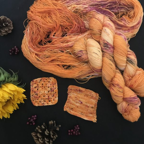 a black background, with pine cones and a closed sunflower. orange skeins, with speckles of brown. yellow and pinky red are shown laid out with twisted skeins on top. there are also knit and crochet swatches in the flat lay.