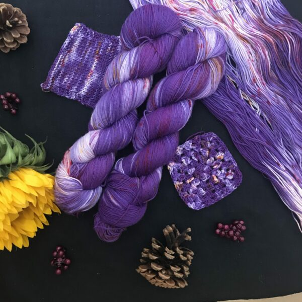 Cadbury purple yarn, with white flashes and speckled with dark pink and orange is shown twisted and untwisted on a black background. There are knit and crochet swathes, pine cones, dark pink fake berries and a closed sunflower in the image also.