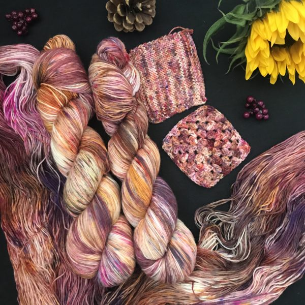 an untwisted skein of yarn flows down the left and along the bottom of the image, with two twisted skeins nestled above. knit and crochet swatches are shown also. The yarn is heavily speckled with reds, browns. oranges, yellows, pinks and purples. Its very autumnal looking! A closed sunflower is in the top right, and two pine cones are also in the image. the background Is black.