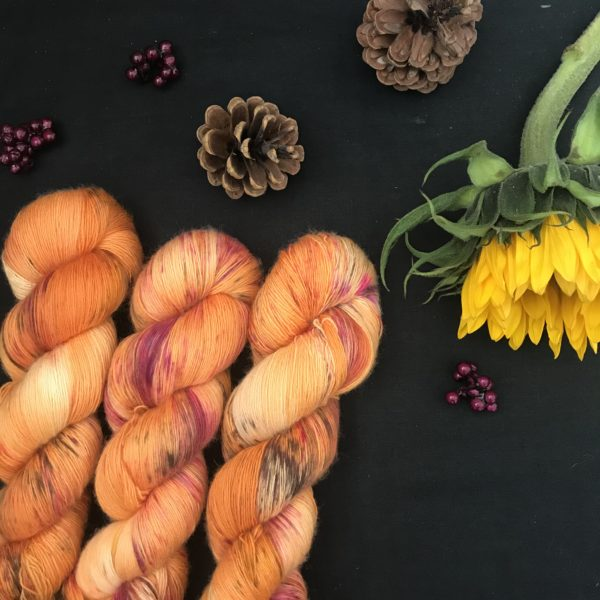 pumpkin orange yarn with speckles or brown and pink is shown twisted on a black background. There are pine cones, dark pink fake berries and a closed sunflower in the image also.