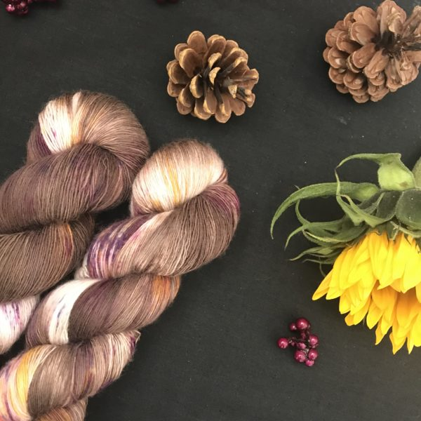 chocolate brown yarn with white flashes and speckles of orange and pink is shown twisted on a black background. There are pine cones, dark pink fake berries and a closed sunflower in the image also.