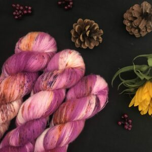 deep, berry pink yarn with white flashes and speckles of brown and orange is shown twisted on a black background. There are pine cones, dark pink fake berries and a closed sunflower in the image also.