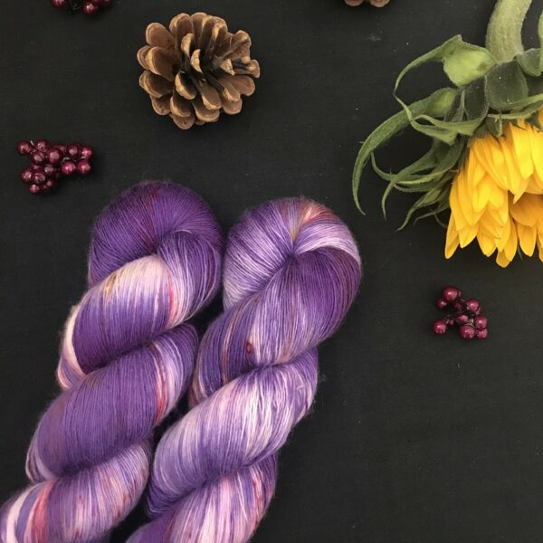 Cadbury purple yarn, with white flashes and speckled with dark pink and orange is shown twisted on a black background. There are pine cones, dark pink fake berries and a closed sunflower in the image also.