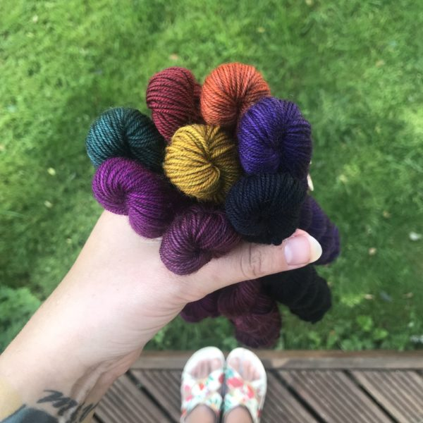 set of 8, rich jewel toned mini skeins, clutched in a white personas left hand. Grass, decking and sanded feet can be seen blurred in the back of the shot. the colours shown are plum, blackberry, purple, navy, dark green, mustard, saffron, deep red and burgundy.
