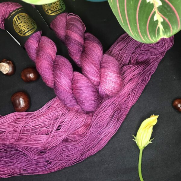 an untwisted skien of pinky plum semi solid yarn lays diagonally across a back background with two twisted skeins on the top. conkers, a closed courgette flower and a maranta plant are also in the shot.