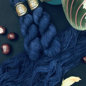 an untwisted skein of deep, dark navy semi solid yarn lays diagonally across a back background with two twisted skeins on the top. conkers, a closed courgette flower and a maranta plant are also in the shot.