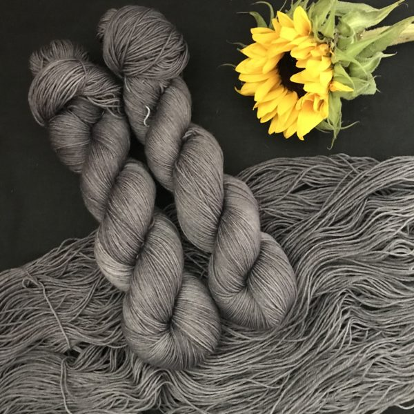 dark grey, stone coloured semi solid yarn, shown twisted and untwisted on a black background. A sunflower is also in the shot.