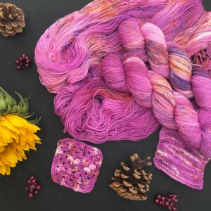deep raspberry pink yarn, with dark and light sections, and speckles of purple and orange is shown twisted, and untwisted on a black background. there are also knit and crochet swatches. the image is scattered with pinecones, dark pink fake berries and a sunflower.