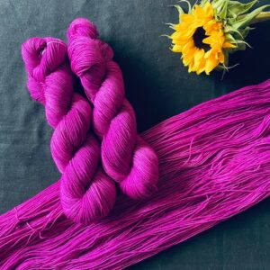 deep berry pink semi solid yarn, shown twisted and untwisted on a black background. A sunflower is also in the shot.