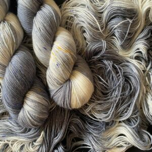 mid blue-grey yarn with white flashes and delicate speckles of yellow and blue