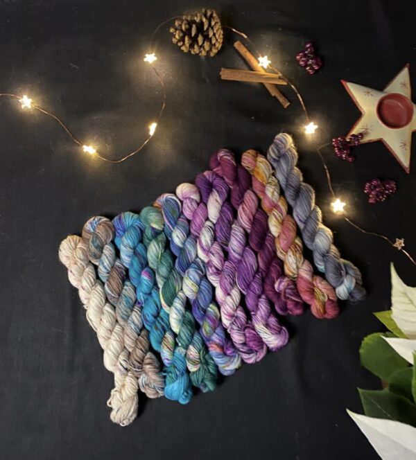 set of 10 mini skeins in assorted colours from the winter range - reds, plums, purples, grey, neutral white, jade green, blues. All are on a black background with a white poinsettia in the shot. Fairy lights are scattered throughout the picture, with cinnamon sticks and a star shaped candle holder also shown.