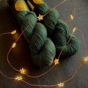 two deep, rich, dark green skeins are on a black background covered with golden star shaped fairy lights. The yarn is super saturated.